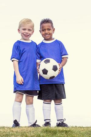 Volle lengte weergave van twee jeugd recreatie voetballiefhebbers. Twee verschillende kleine jongens die zich op een grasgebied bevinden Stockfoto