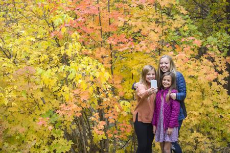 Gelukkige tienermeisjes die selfie in park met mobiele telefoon nemen Stockfoto