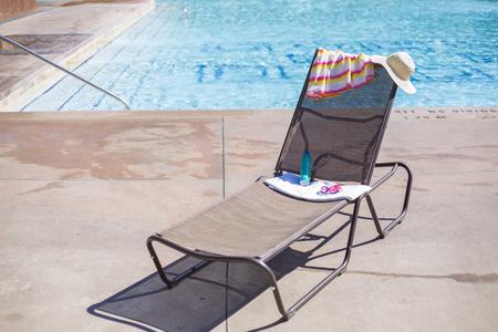 Lounge stoel bij een zwembad met zonnebrandcrème en een handdoek. Geweldige generieke tropische vakantiefoto met kopie ruimte