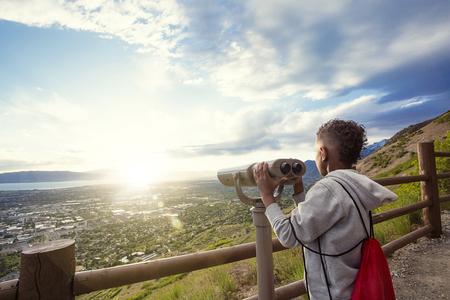 Jonge jongen kijkt uit door een verrekijker op de berg uitzicht op de stad beneden na een bergwandeling wandelen. Stockfoto