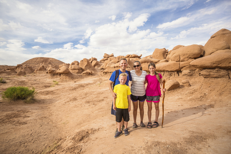 Cute young family on a vacation together. Hiking among the red rock formations around Moab, Utah and Arches National park. Banco de Imagens