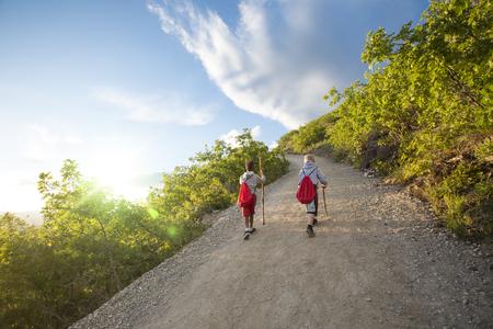 Mening van erachter van twee jongens die samen op een schilderachtige bergsleep op vroege de zomerdag wandelen. Actieve kinderen hebben samen een avontuur in zomerkamp Stockfoto