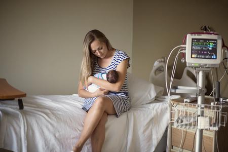 Jonge moeder die haar houdt Vroeggeboren baby die in het ziekenhuis wordt behandeld. Met liefde en tederheid houdt ze haar baby dichtbij zittend op een ziekenhuisbed naast een monitor voor vitale functies