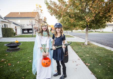 Groep kinderen gekleed in kostuums van Halloween die truc gaan of in openlucht in oktober in een verfraaide buurt behandelen