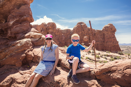 Cute young family on a vacation together. Hiking among the red rock formations near Moab, Utah and Arches National park.