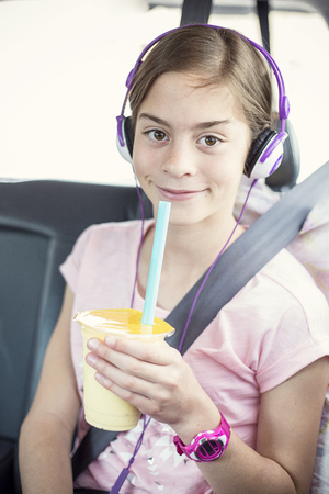 Cute smiling girl on a long car ride listening to music and drinking while safely strapped in a car seat