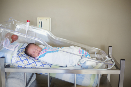 De babyjongen die van de slaap in een het ziekenhuisvoederbak rust in een ruimte van de het ziekenhuislevering. Het etnisch diverse kind is vredig en tevreden in zijn bed Stockfoto
