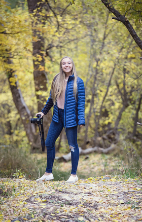 Een schattig blond glimlachend tienermeisje dat haar camera houdt die foto's neemt tijdens een mooie herfstdag in openlucht. Tiener die een pret met haar artistieke hobby heeft