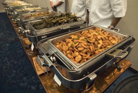 groot dienblad met garnalen en andere gerechten bij een groot verzorgd banketbuffet Stockfoto