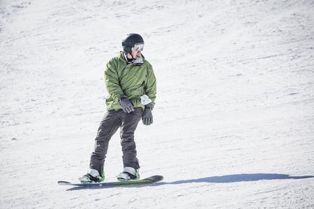 Mannelijke volwassen snowboarder die onderaan een verzorgde sneeuwheuvel berijdt. Een mooie dag op de hellingen met plezier