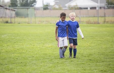 Twee voetbalteamgenoten lopen het veld uit na een verlies. Conceptenfoto van aanmoediging van vrienden na teleurstelling van een verlies