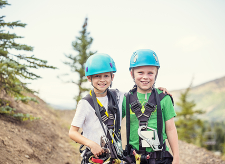 Twee lachende kinderen klaar om te gaan op een zip line avontuur in de bergen, terwijl op een zomervakantie samen. Helmen dragen en een geweldige tijd hebben
