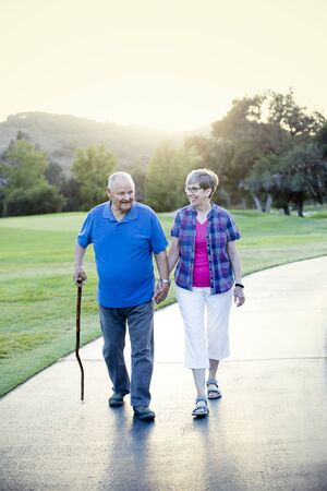 Senior couple holding hands and walking together outdoors on a sunny day