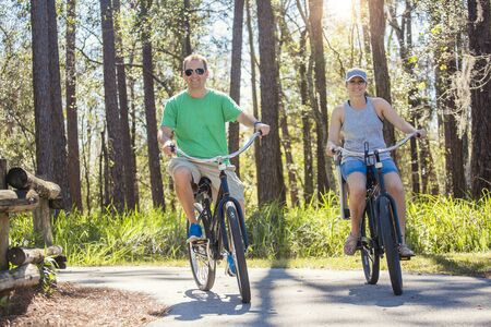 Happy attractive couple on a bike ride together outdoors on a bicycle path in the woods. Bike rental photo Foto de archivo