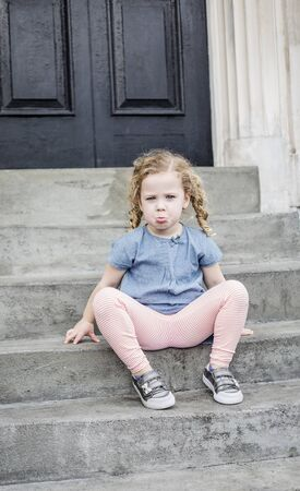 Emotional portrait of a sad, unhappy little girl with blond curly hair sitting on the front steps of her home in an urban setting. Cute expression and adorable face. child behavior concept photo
