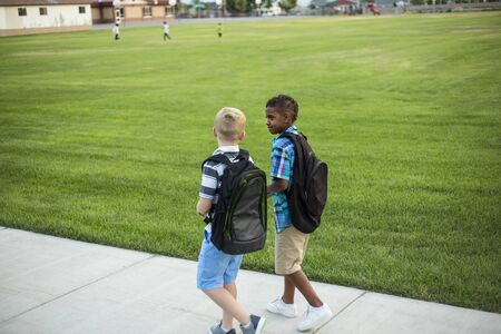 Two diverse school kids walking and talking together on the way to school. Back to school photo of diverse school children wearing backpacks in the school yard