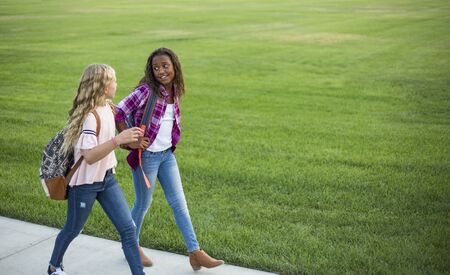 Two diverse school kids walking and talking together on the way to school. Back to school photo of diverse girls wearing backpacks in the school yard