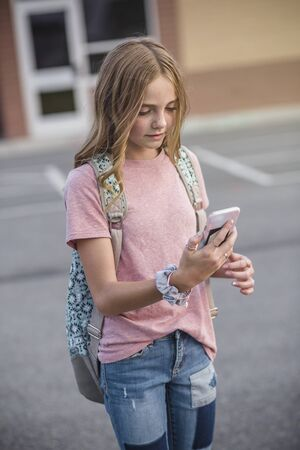 Cute teenage girl walking to school using her cell phone and connecting with friends