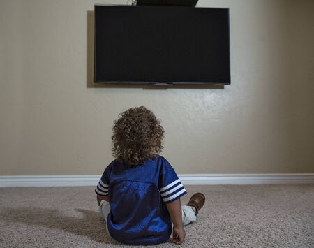 Rear view of a young child watching Television while sitting on the floor of his home. Selective focus on the back of the curly-haired diverse little boy watching sports on TV 写真素材