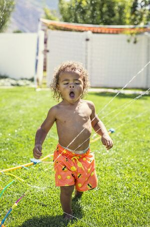 Cute little boy drinking from the sprinklers in the backyard on a hot summertime day. African American boy playing in the outdoors trying to stay cool on a warm summer day Stock Photo