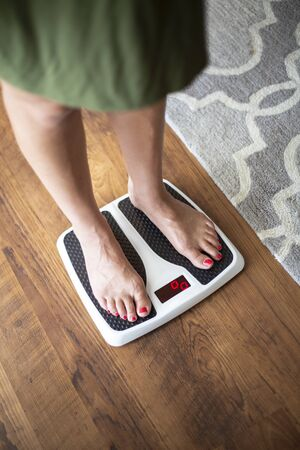 Closeup photo of a Woman standing on a digital weight scale Stock Photo