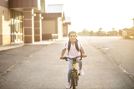 Diverse Young girl riding her bicycle home from school. Education concept photo of diversity in school Stock fotó