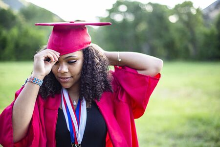 Candid Portrait of a beautiful multiethnic woman putting on her graduation cap and gown. Selective focus on her beautiful face