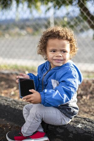 Young diverse boy using his parent`s smartphone at a park outdoors. Concept photo of children who are being raised screen dependent