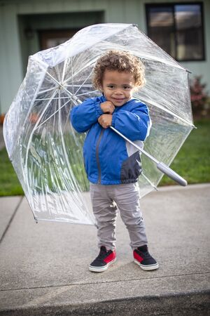 Cute little boy holding an umbrella as he leaves his home to go outside on a raining day. Smiling and ready to play despite the rainy weather