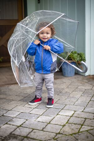 Cute little boy holding an umbrella as he leaves his home to go outside on a raining day. He is looking up checking for raindrops. Stock fotó