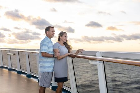 Middle aged couple enjoying a Caribbean Cruise vacation together. Candid photo of a couple enjoying their time on board a cruise ship together. Walking along the deck at sunset and laughing together
