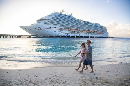 Middle aged couple enjoying a Caribbean Cruise vacation together. Candid photo of a couple holding hands and walking together on a beach with a Cruise ship in the background