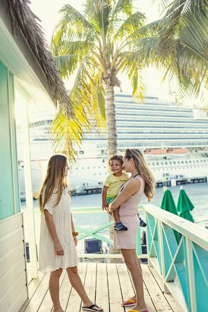 A smiling cute family enjoying a Caribbean Cruise vacation together. Candid photo of a young family talking together with a Cruise ship in the background Stock fotó