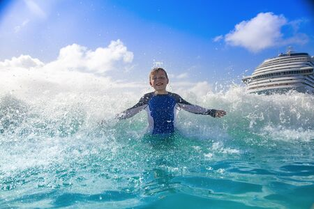 Happy Boy playing in the ocean waves while on a Cruise vacation. Aqua blue Caribbean sea water splashing the boy from behind on a warm day in the islands.