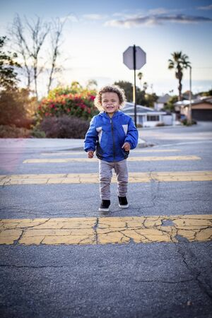 Cute, young bi-racial child walking across the street at the crosswalk. Safety first photo of boy going to preschool early in the morning.