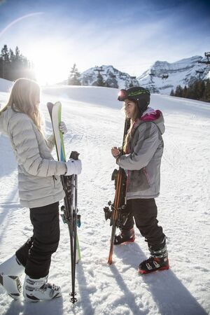 Two young female skiers talking together after a day of skiing on the slopes. Smiling lifestyle photo of young skiers