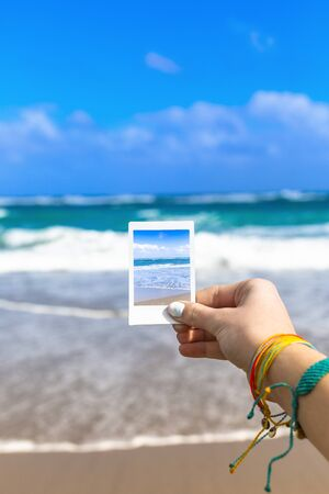 Girl Hand Holding Instant Photo Of Sea Beach Landscape, focus on hand and photo. Great abstract tropical travel photo. Banco de Imagens
