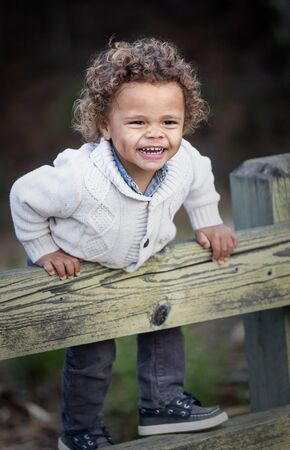 Portrait of a Happy cute young diverse boy outdoors. Excited and fun expression of a biracial little child. Stock fotó
