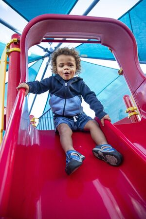 Happy cute young diverse boy with enjoying a ride down playground slide at an outdoor park. Excited and fun expression