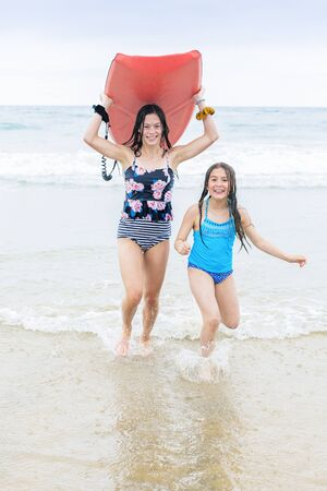 Full length photo of two cute teen girls running on a beautiful beach carrying a bodyboard. Having fun in the sun while on a family beach vacation. Stock fotó
