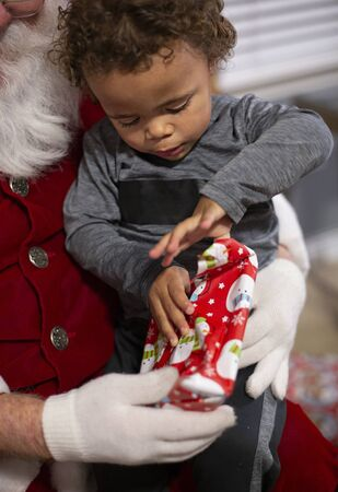 Close up view of a Young bi-racial child opening a Christmas present on Santa`s lap. Santa Clause giving a cute little boy a present that he is unwrapping with excitement