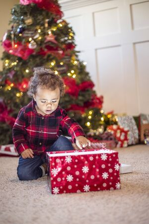 Cute little diverse boy opening a magical Christmas present in front of a Christmas tree. Excited expression on the child's face as he looks inside the box