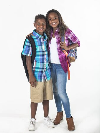 Two cute smiling African American school kids isolated on a white background. Full length photo of a diverse boy and girl. Education concept photo