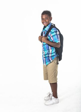 Smiling African American school boy on white background. Wearing a backpack and a plaid shirt and ready to go to school. side view Stock fotó