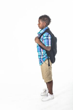African American school boy on white background. Wearing a backpack and a plaid shirt and ready to go to school. side view Category Stock fotó