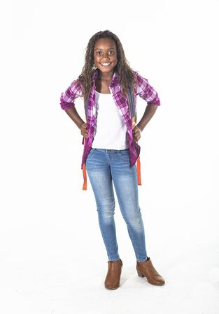 Smiling African American school girl isolated on white background. Wearing a backpack and a plaid jacket and ready to go to school. Front view