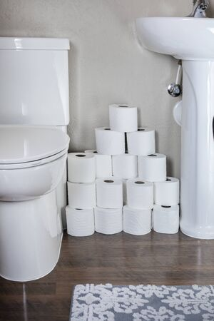 Large stack of toilet paper rolls in a residential bathroom. Home preparedness for emergency situations. Stocking up on the essentials.