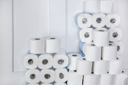 Large stack of toilet paper rolls in a home. Home preparedness for emergency situations. Stocking up on the essentials.