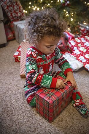 Cute black little boy unwrapping a Christmas present on Christmas morning.