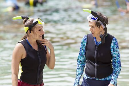 Candid lifestyle photo of two women, including a senior woman, snorkeling together at an outdoor resort. Tourism and family vacations for seniors and adults